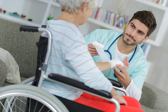 nurse doing bandages on an old lady on wheelchair