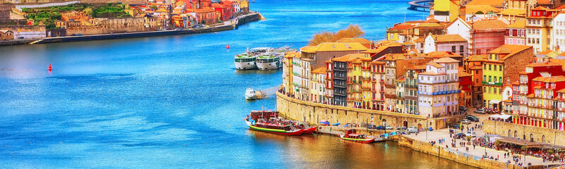 Spoed Fotobehang Europese Plekken Porto, Portugal old town ribeira aerial promenade view with colorful houses, Douro river and boats, banner panoramic view