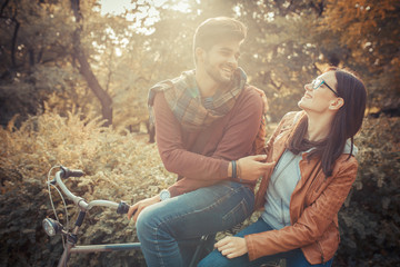 Young couple sitting on bicycle at the park on autumn day.Love  couple concept.
