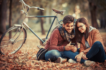 Young couple sitting outdoors at the park on beautiful autumn day.They sitting leaves and using smart phone.