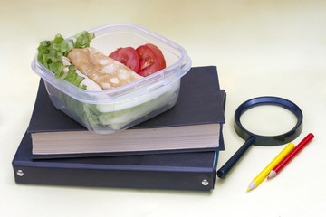 Plastic container, lunchbox with school lunch on a yellow background