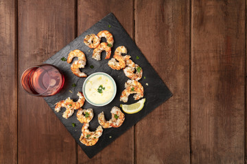 Overhead photo of shrimps on a dark rustic background, with a sauce and a glass of rose wine, with place for text