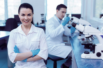 Experienced scientist. Professional delighted positive woman smiling and looking at you while standing in the biological laboratory