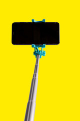 Monopod for selfie with smart phone. Selfie stick with smartphone isolated on yellow background