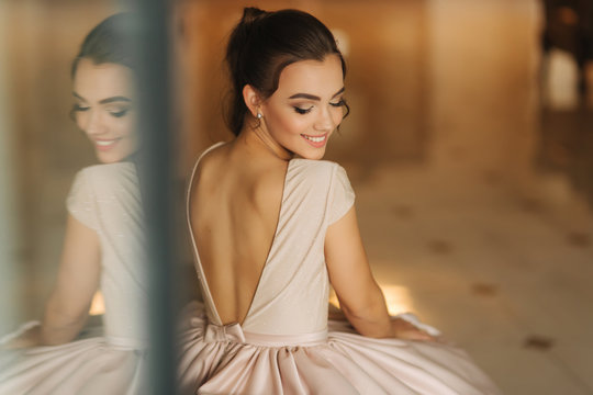 Beautiful stunning young lady in amazing dress sitting on luxury armchair