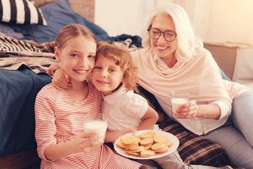 Harmonious relations. Cute grandchildren embracing while posing for the camera with a plate of homemade cookies and their granny sitting next to them.