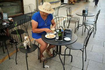 "A person eats a breakfast, coffee, and bread with olive oil, at ""La Chocolaterie"" coffee shop in downtown Ronda"