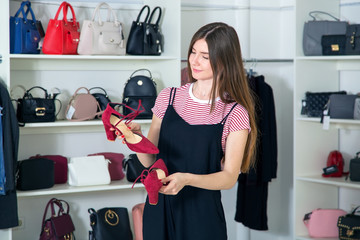 Buy red shoes. A woman salesman in a clothing store and shoes. Small business.