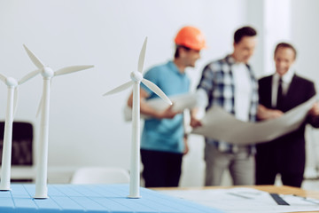 Tiny windmills. Group of three qualified responsible engineers discussing the construction of windmill generators