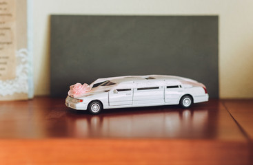 Miniature white wedding car limousine. Collection of retro automobiles. Wedding car decoration.