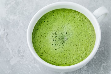 Japanese green tea latte in white cup on gray background