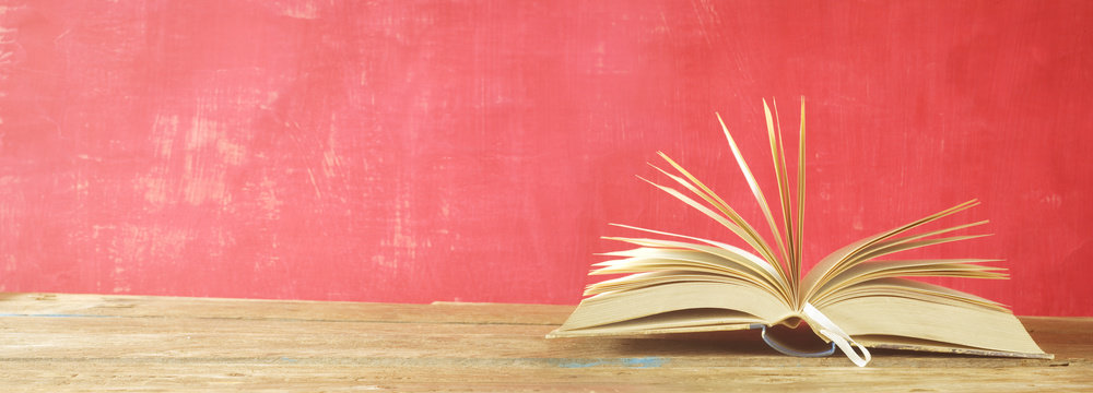 Open book on red grungy background, panoramic, good copy space, reading learning, literature concept.