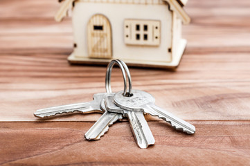 Keys with model of house on the wooden background. Real estate concept.