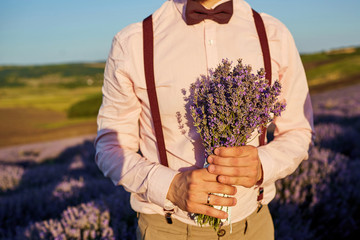Close-up of a bouquet of lavender in the hands of the groom in the field of lavender.