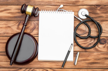 Blank notepad with gavel and stethoscope on wooden table. Top view.