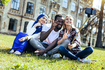 Peaceful mind. Excited young people smiling broadly while sitting outdoors and gesturing with a peace sigh for a selfie.