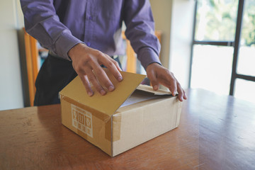 Selective focus of young man unboxing a parcel