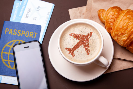 Mug of coffee with an airplane on the foam. Morning coffee with croissant in flight. Paspor and ticket with smrtrfonom