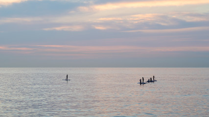 Team of young women standing up on a paddle surf board, enjoying a beautiful sunrise on the ocean