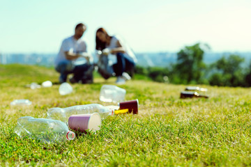 Lets clean it. Focused photo on rubbish that lying on the grass, attentive volunteers collecting plastic