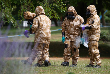 People in military hazardous material protective suits collect an item and photograph its location in Queen Elizabeth Gardens in Salisbury
