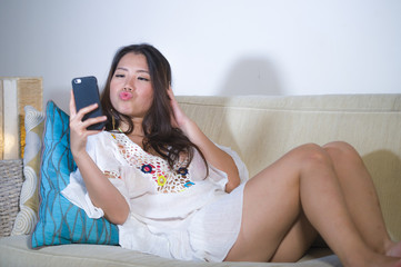beautiful happy Asian Korean woman lying at home sofa couch using internet dating app in mobile phone taking selfie portrait in fish mouth expression