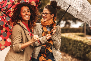 Two female best friend walks at the city street with umbrellas above head.They smiling and making fun.Raining day and autumn concept.