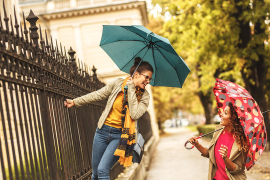 Two female best friends making fun at the city street.Raining day and autumn concept.