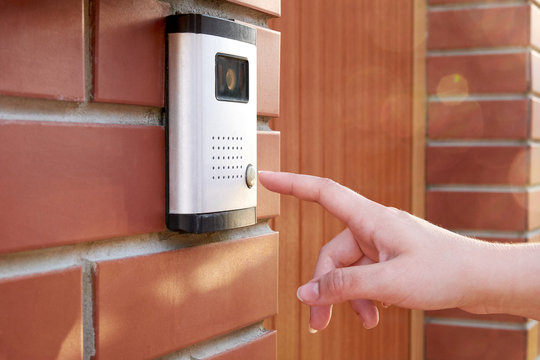 The female hand presses a button doorbell with intercom