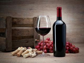Weinflasche mit Korken, Trauben, Glas Wein, Weinkiste auf Holztisch mit Holzhintergrund