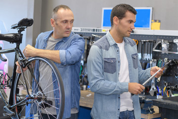 two bicycle repairer colleagues working in bike garage