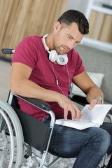 disabled man in wheelchair reading a book