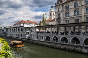 Slovenia, 24/06/2018: vista dello skyline del centro di Lubiana, la capitale slovena, con una barca turistica in navigazione naviga sul fiume Ljubljanica