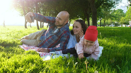 Happy family is laying on the grass and father doing selfie with a baby at sunset in the park