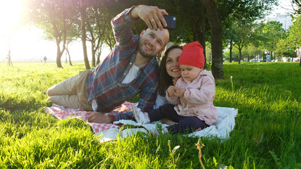 Happy family is laying on the grass and father doing selfie with a baby at sunset in the park on the smartphone