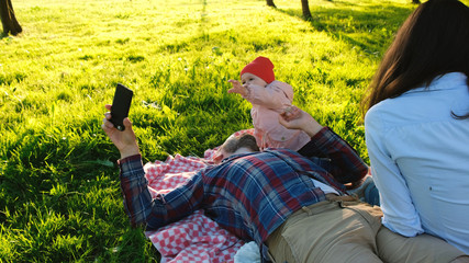 Young family is resting on nature, a small child asks for a smartphone, the father takes away the phone from the baby