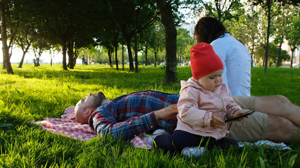 Little girl is playing with a smartphone in nature. Young family is resting in the park