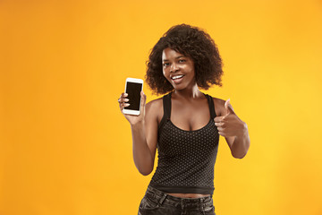 Portrait of a confident casual afro girl showing blank screen mobile phone