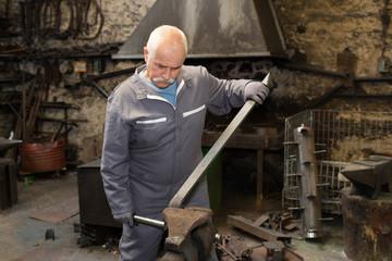 senior blacksmith forging the molten metal