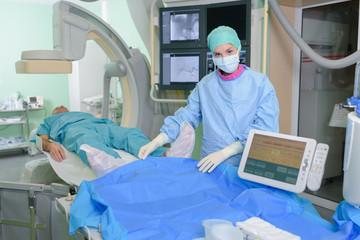 Nurse in scrubs with patient under scanner