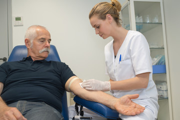 Nurse taking blood from elderly male patient
