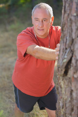 elderly man stretching on a tree