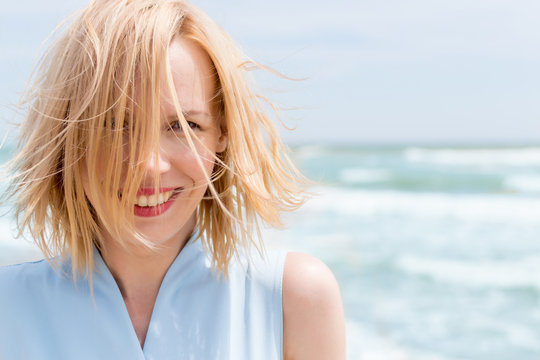A middle-aged woman smiles with disheveled hair on vacation against the background of the sea.