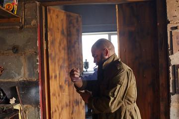 Man's den workshop inside man rolling up sleeves before work