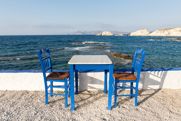Table and chairs standing on the coast of Aegean sea in Greek island of Milos