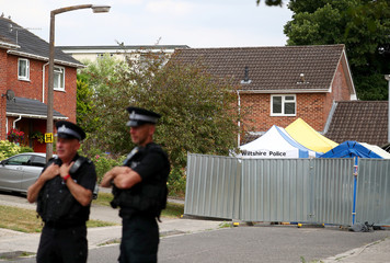 Police officers stand on duty outside Sergei Skripal's home in Salisbury
