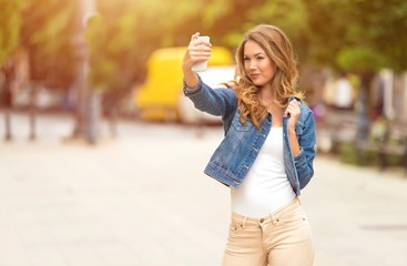 Beautiful woman taking a selfie with her phone