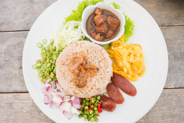 """Kao Cluk Ka Pi or Mixed Cooked Rice with Shrimp Paste on the wooden round dish. Thai Traditional food."