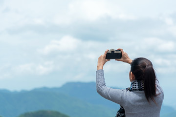 Traveler woman taking photo with her phone of the view natural mountain in the winter day  morning, relax and freedom lifestyle.  Travel Concept