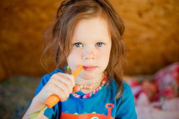 Little girl eats a carrot